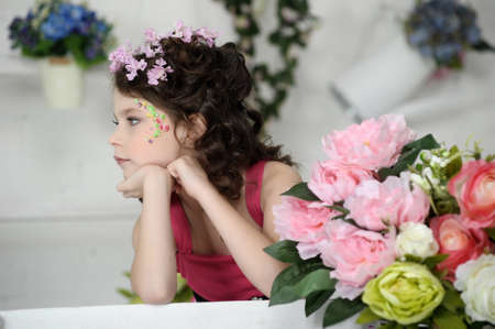 portrait of a girl with flowers in her hair, and in the hands of Stock Photo - 19397312