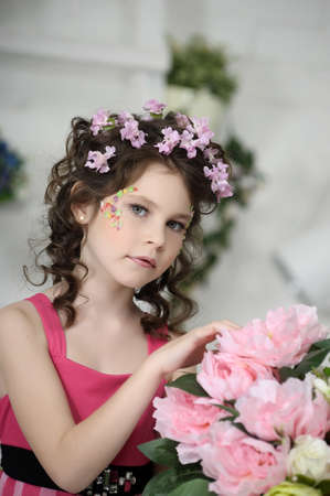 portrait of a girl with flowers in her hair, and in the hands of Stock Photo - 19397320