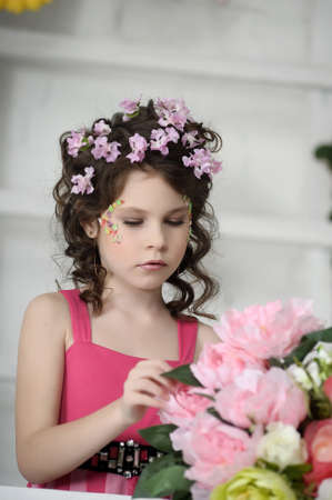 portrait of a girl with flowers in her hair, and in the hands of Stock Photo - 19338946