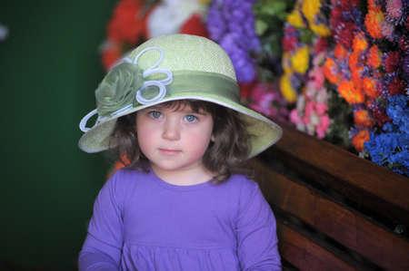 kleines Mädchen in einem Hut auf der Bank