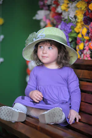 little girl in a hat on the bench photo