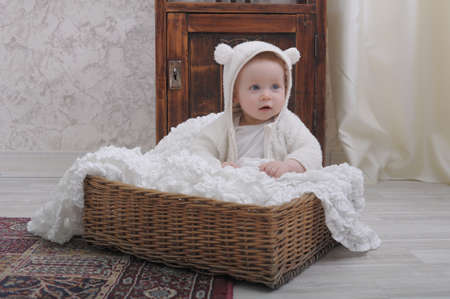 toddler sitting in a wicker basket photo