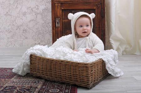 幼児の枝編み細工品バスケットに座っています。