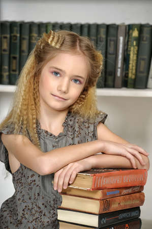 girl holding a pile of books in the library Stock Photo - 19353687