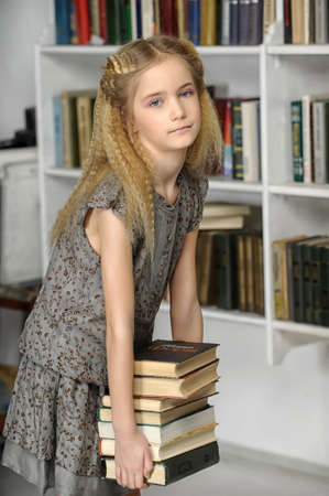 girl holding a pile of books in the library photo