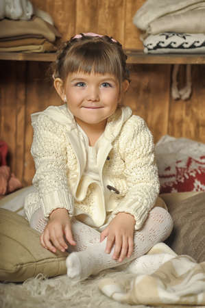 the little girl next to the wardrobe with warm clothes Stock Photo - 19338768