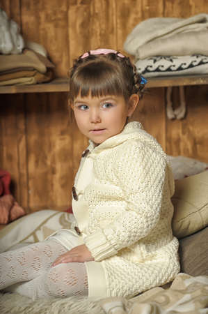 scallywag: the little girl next to the wardrobe with warm clothes Stock Photo
