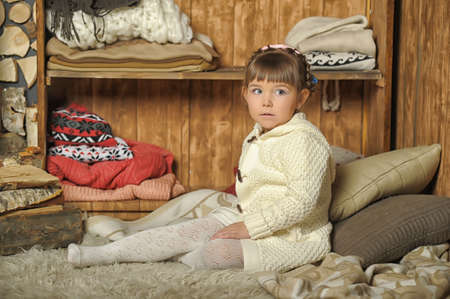 spalpeen: the little girl next to the wardrobe with warm clothes Stock Photo