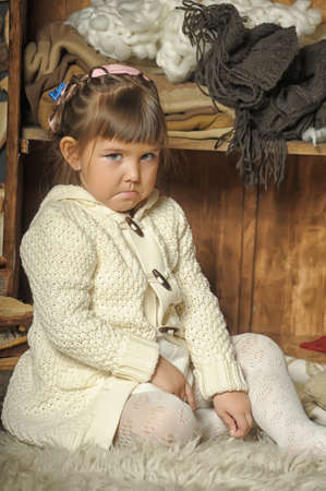 prankster: the little girl next to the wardrobe with warm clothes Stock Photo