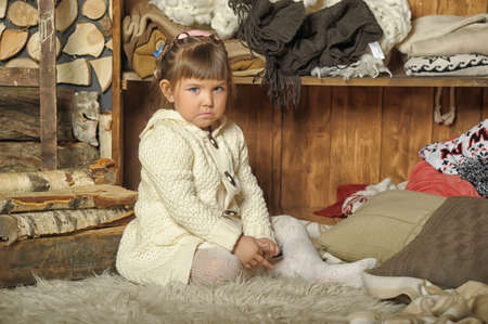 the little girl next to the wardrobe with warm clothes Stock Photo - 19338940