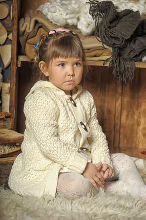 the little girl next to the wardrobe with warm clothes Stock Photo - 19338772