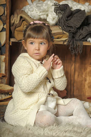 the little girl next to the wardrobe with warm clothes Stock Photo - 19338769