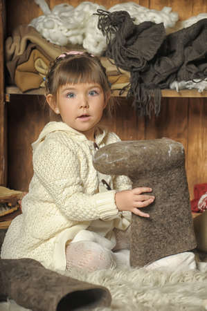 the little girl next to the wardrobe with warm clothes photo