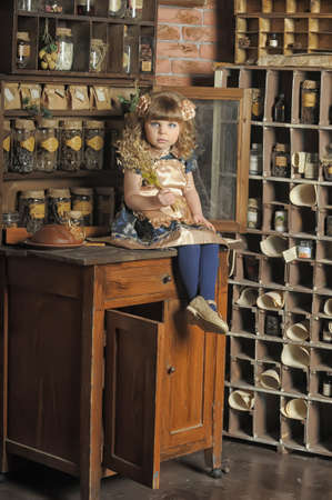 a little girl dressed in retro style on the old kitchen photo