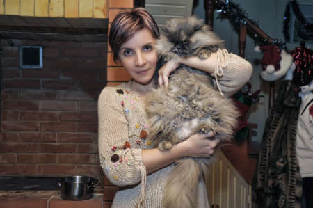 girl holds a large cat in her arms photo
