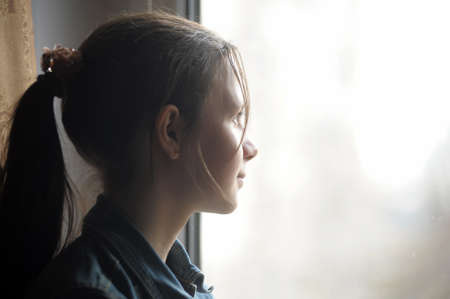 teen girl looking out the window Stock Photo