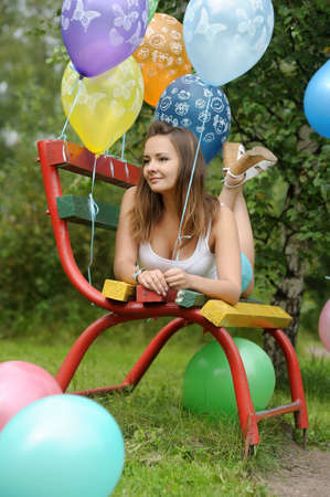 quietly: teenage girl on a bench in the park with balloons