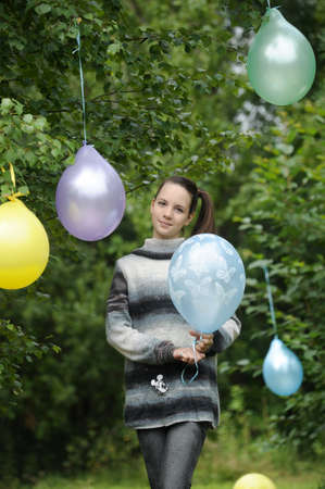 Young girl with colorful latex balloons photo