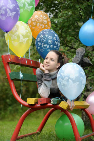 teenage girl on a bench in the park with balloons photo