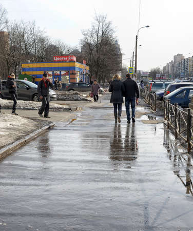 passers-by on the street after a rain, in St. Petersburg, Russia