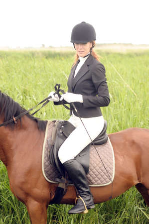rearing: young woman in a suit riding a horse Stock Photo
