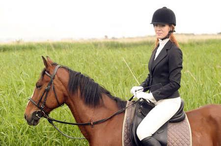 jonge vrouw in een pak op een paard