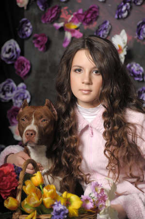 Beautiful girl with dog on a floral background photo