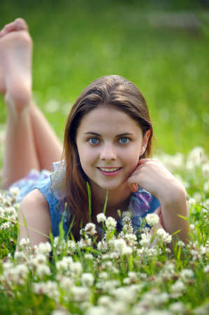 preteens girl: Smiling preteen girl lying down on green clover background