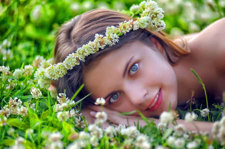 Smiling preteen girl lying down on green clover background photo