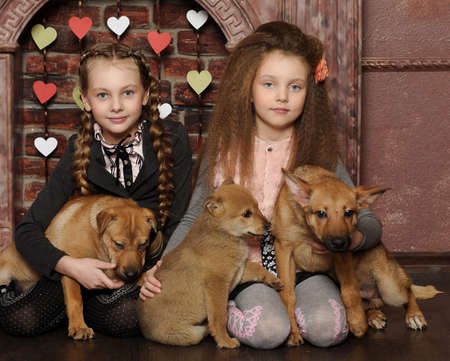 Two sister girls with puppies Stock Photo - 27608036