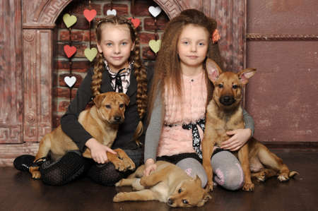 Two sister girls with puppies Stock Photo - 27608076