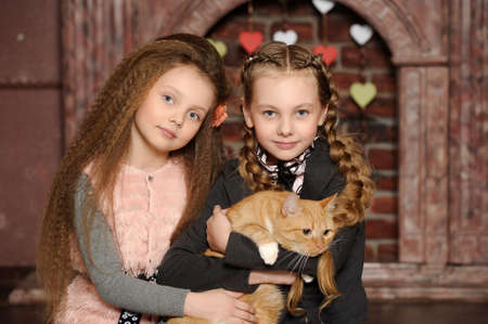 Two sister girls with a cat Stock Photo - 27608100