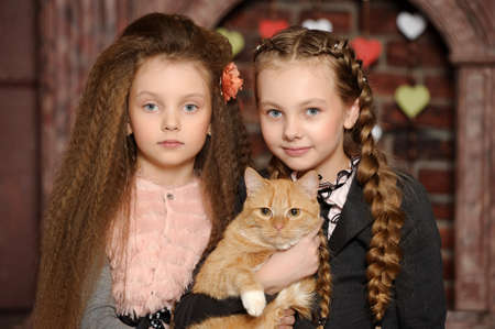 Two sister girls with a cat Stock Photo - 27608132