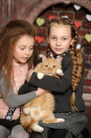 Two sister girls with a cat at home Stock Photo - 27608133