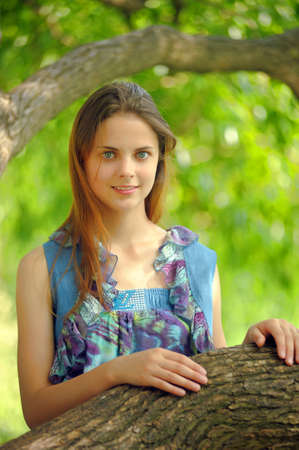 Portrait of a beautiful young teenager girl near a tree in summer   photo