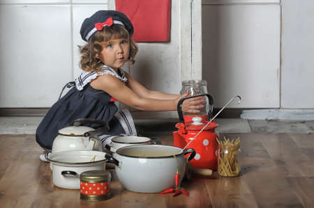 sailor girl: Small sailor girl drinking tea and eating a muffin in the kitchen