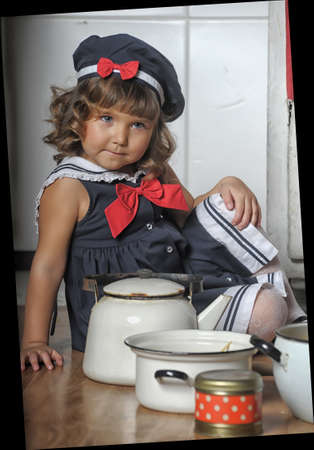 Small sailor girl drinking tea and eating a muffin in the kitchen  photo