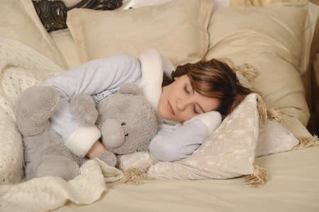 Woman sleeping with teddy bear photo