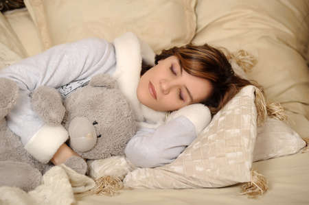 inocent: Woman sleeping with teddy bear Stock Photo