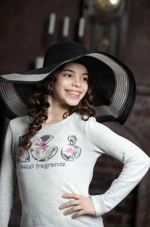 teen girl in curly hair in a wide-brimmed hat Stock Photo - 21997261