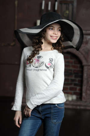 teen girl in curly hair in a wide-brimmed hat photo