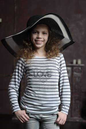 teen girl in curly hair in a wide-brimmed hat Stock Photo - 21997296