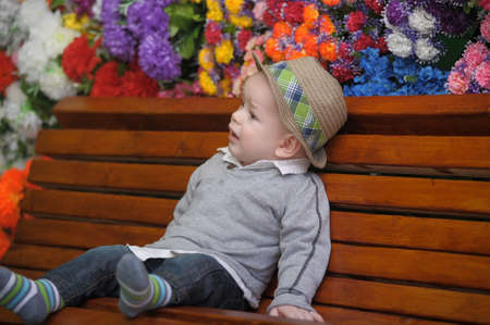 little boy on a bench with a hat photo