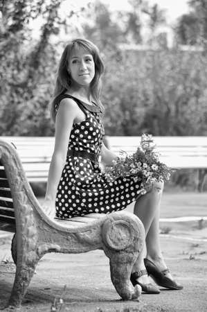 a woman with a bouquet of wild flowers sitting on a bench in retro style photo photo
