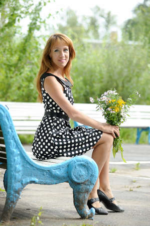 a woman with a bouquet of wild flowers sitting on a bench in retro style photo