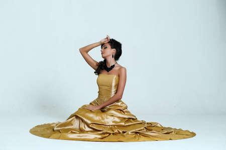 beautiful brunette in gold dress photo