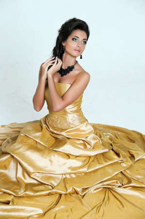 beautiful brunette in gold dress photo