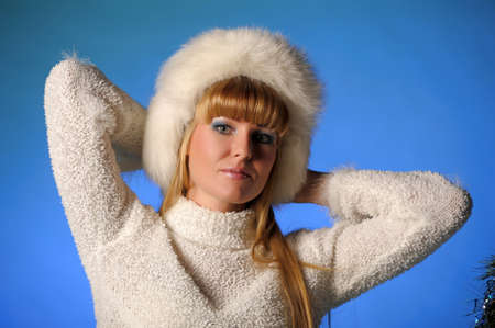 beautiful blond woman in a fur cap on a blue background Stock Photo - 21805251