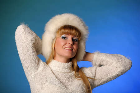 beautiful blond woman in a fur cap on a blue background Stock Photo - 21805253