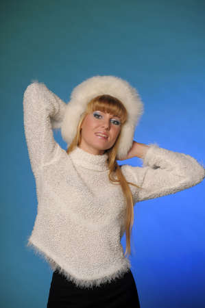 beautiful blond woman in a fur cap on a blue background photo